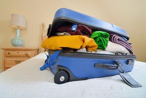 overflowing luggage on a bed