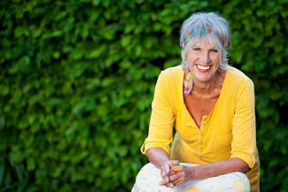Portrait of happy senior woman sitting against creepers in park